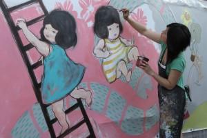 Une femme peint une fresque