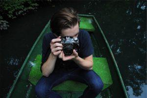 Un homme prend une photo dans une barque